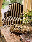 Period armchair with striking striped upholstery and silver teapots and tray on recycled wood coffee table