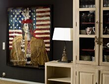Modern painting with collage elements of Native American against Stars and Stripes next to glass-fronted, country-style cabinet