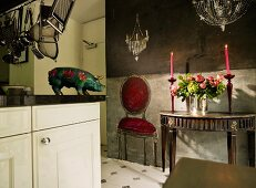 Flowers and candles on antique console table against trompe l'oeil painting of upholstered chair and chandeliers; inquisitive china pig on kitchen worksurface