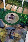 Landscaped garden with fire pit on circular hearth and objets d'art on tiled terrace