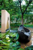 Stone, boat-like artwork next to pond and waterspout in wall in landscaped garden