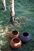 Group of clay pots of various colours on lawn