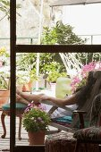View through French windows onto terrace with greenery - woman sitting on lounger with feet propped up on antique stool