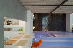 Orange bar stool at kitchen counter in front of dramatic, lavender blue bathroom landscape with sunken spa tub and romantic mural