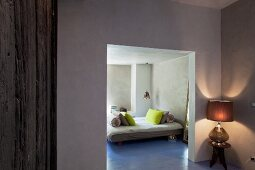 View through open doorway into purist bedroom with lime green pillows on double bed