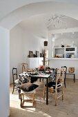 Stühle aus naturgewachsenen Hölzern an gedecktem Esstisch mit lässig übergeworfener, schwarzweiss karierter Decke