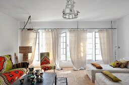 Sofa, Sessel und Dekokissen mit Bezügen im nordafrikanischen Stil; gemusterte Porzellanvasen auf Couchtisch