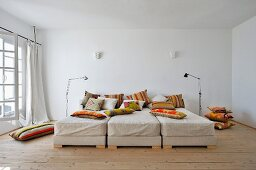 Viele orange gemusterte Dekokissen und drei aneinander gereihte Betten mit naturhaftem Leinenbezug
