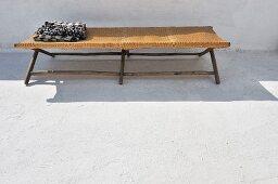 Schwarzweisses Tuch auf einfacher, nordafrikanischer Liege in einem Innenhof
