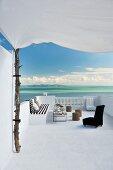 Afrikanische, niedrige Sessel und Sonnensegel an Baumstamm auf Terrasse mit traumhaftem Meerblick