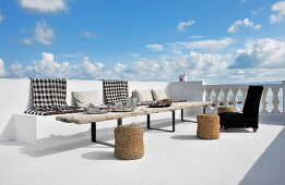 Schwarzweiss karierte Decken auf gemauerter Bank und rustikaler Holztisch mit Basthockern auf Terrasse am Meer