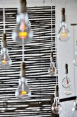 Simple, hanging bare bulbs in front of a see through, wicker, room divider