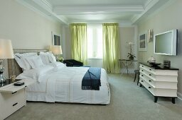 Double bed with upholstered headboard opposite post-modern chest of drawers in classic bedroom