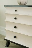 Black and white, post-modern chest of drawers with concave drawer fronts