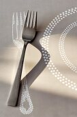 Fork on pale grey paper place mat with fork and plate motif