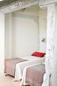 Elegante Einzelbetten in Nische eines rustikalen Schlafzimmers mit geweisselter Holzkonstruktion
