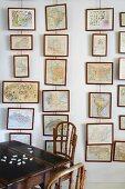 Bilder übereinander am Drahtseil vor Wand aufgehängt und traditioneller Holztisch mit Stühlen aus dunklem Holz