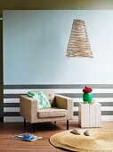 Insubstantial wire lampshade against pale wall; dado with grey horizontal stripes behind comfortable armchair