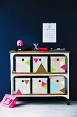 Storage boxes decorated with colourful triangles on retro-style shelving unit on castors against dark wall