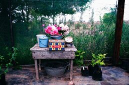 Old tins and summer bouquet in bucket on rustic wooden table in work space on terrace in cottage garden