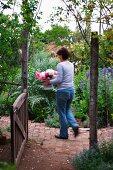 View through open garden gate of woman walking through wild cottage garden holding bouquet