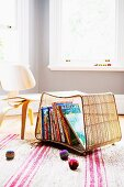 Woven storage basket on the floor for picture books; 50's style child's chair and colorful juggling balls