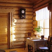 Board game on tablecloth on table and simple wooden chairs below window in corner of log cabin
