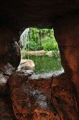 View through small mouth of stone cave and waterfall to pond landscape beyond