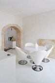 Dining area with designer shell chairs in white minimalist room with historical arched doorway