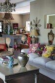 Silberne Vase auf Couchtisch und folkloristische Kissen auf Sofa in offenem Wohnraum, im Hintergrund der Küchenbereich