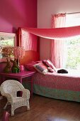 Romantisches Mädchenzimmer in Rottönen mit weißem Rattanstuhl und pinkfarbenem Nachttisch, Bett mit gemusterter Tagesdecke unter Baldachin