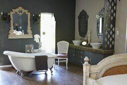 Freistehende Vintage Badewanne vor grauer Wand und Spiegel mit geschnitztem Rahmen in grossräumigem Bad