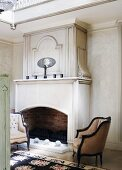 Antique-style upholstered armchairs in front of open fireplace in elegant interior