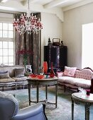 Antique sofas and pretty crystal chandelier above round side table in romantically inspired interior