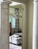View between two pillars into bedroom with walls painted pastel green and chandelier; two ottomans on castors as bedroom bench