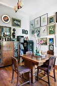 Dining room with elegant vintage furniture, collection of pictures on walls and various objets d'art