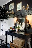 Bathroom with black-painted walls, white wall tiles, wrought iron standard candelabra and black vintage washstand