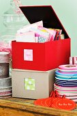 Colourful correspondence cards and ribbons in fabric-covered storage boxes