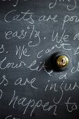 Writing on wall painted with chalkboard paint and brass light switch