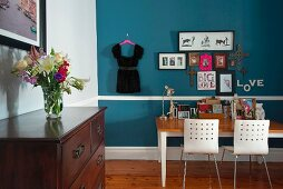 Desk and two chairs against blue wall; bouquet on traditional chest of drawers in foreground