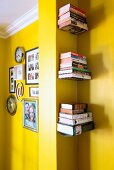 Pictures and clocks on yellow wall separated from floating bookshelves in niche by pillar