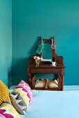 Bed with colourful scatter cushions and antique dressing table and stool in turquoise bedroom