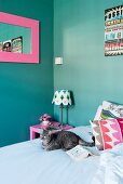 Cat and colourful scatter cushions on bed; pink-framed mirror on turquoise wall
