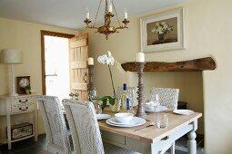 Esszimmer mit weissen Korbstühlen an gedecktem Landhaustisch in elegantem Ambiente