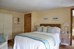 Hellblaue Accessoires im gediegenen Landhaus Schlafzimmer mit Bad Ensuite