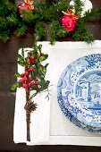 Place setting with blue and white crockery on pulled thread work place mat and small posy with pinecone and red berries as festive table decoration