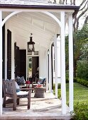 Terrassenmöbel aus Holz auf sonniger Veranda mit Zugang zum Garten