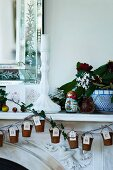 Tiny buckets with numbered labels as Advent calendar hanging from traditional mantelpiece