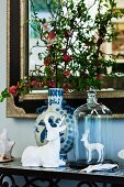 White china stag figurines and ceramic vase of flowering branches in front of elegant mirror