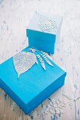 Finely carved leaf motifs decorating blue gift boxes